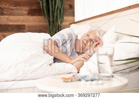 Sick Senior Woman In Bed, At Home.