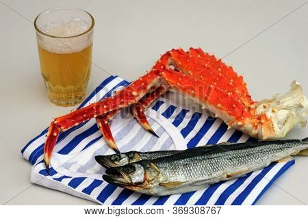 The Striped Vest. Kamchatka King Crab And Dried Fish On It. Beer Snack. Glass Of Beer.
