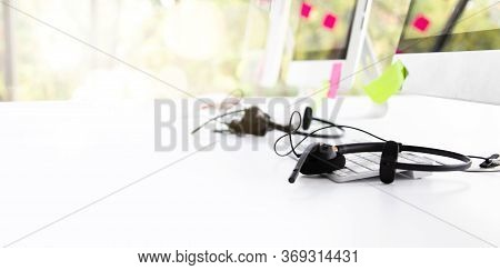 Voip Headset On Desk With Computer Desktop At Customer Service And Marketing Support Workplace. Offi