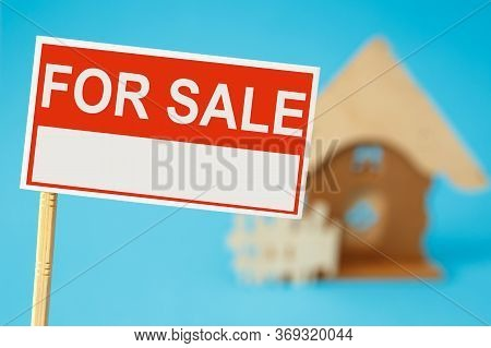 A Sign For The Sale Of Real Estate And A House In The Background. Real Estate Sale Concept