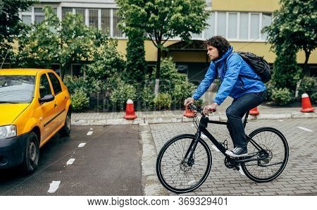 Outdoor Horizontal Image Of Handsome Man Cycling On His Bike Down The Street Next To The Building. C