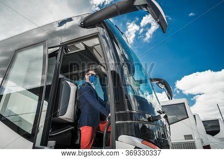 Charter Motor Coach Bus Driver Wearing Virus Outbreak Mask Awaiting Vacation Destination Passengers.