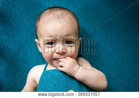 Cute Newborn Baby On A Blue Blanket.  Crying Baby In His Bed. Closeup Portrait Of Newborn Baby. Baby