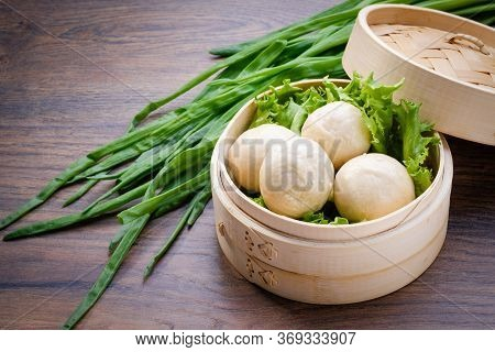White Bread Buns In Traditional Bamboo Steamer On Wooden Table Background. Traditional Asian Steamed