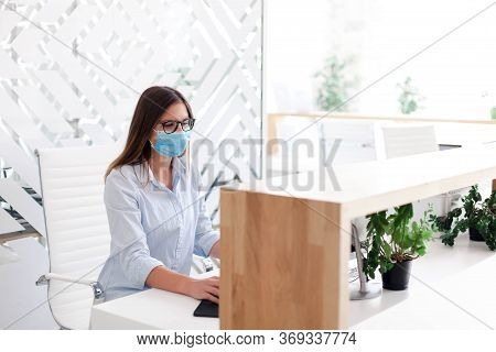 Receptionist Wearing Medical Mask In Office. Protection Employees On Workplace. Young Woman Working