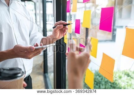 Young Creative Team Professional Using Post It Notes In Glass Wall To Writing Strategy Business Plan