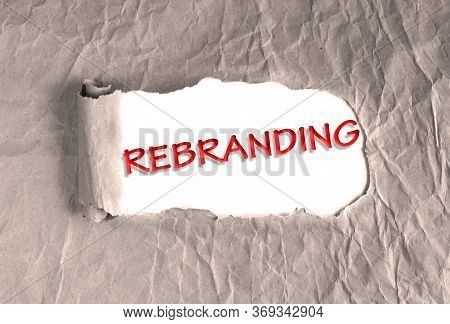 Word Rebranding On Torn Brown Grunge Paper Background. Marketing Strategy, Different Trajectories In