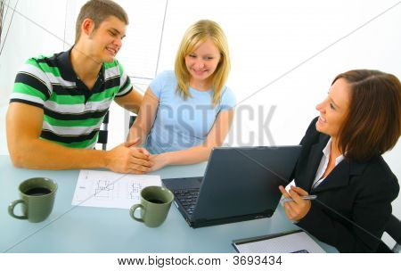 Young Couple Talking To Real Estate Broker