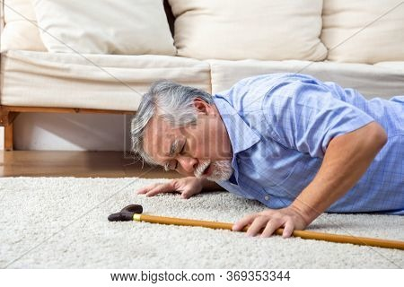 Asian Senior Man Falling Down On Carpet And Lying On The Floor In Living Room At Home, Falls Of Olde