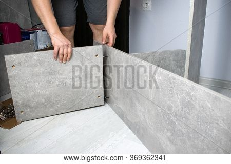 Man Collects A New Wood Gray Cupboard. Carpenter Collects A Locker, Fixes The Walls Of The Furniture