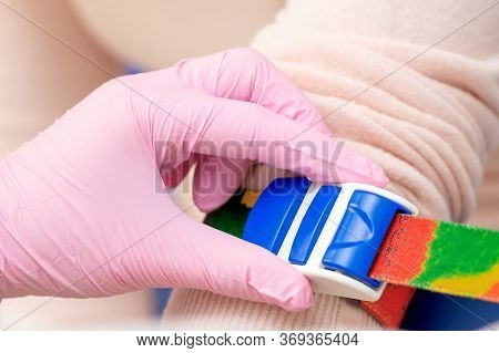 Nurse Hand Is Tightening The Harness On The Arm To Take Blood From A Vein, Close Up.