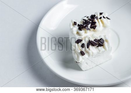 Two White Marshmallows Poured With White Chocolate. Marshmallows On A White Plate. Dessert Of The Ar