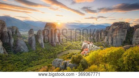 Panoramic view of Meteora, Greece at romantic sundown time with real sun and sunset sky. Meteora - incredible sandstone rock formations.  The Meteora area is on UNESCO World Heritage