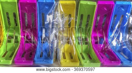 Jumbo Clothespins. Extreme Closeup. Back Of Colourful Plastic Clothespins Wrapped In Cellophane. Sto