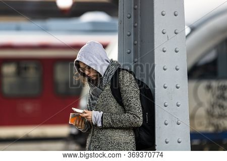 Young Woman Using Cell Phone On The Train Platform At Bucharest North Railway Station (gara De Nord