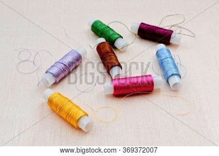 Silk Threads For Embroidery On A Beige Background. Skeins Of Yellow, Lilac, Burgundy, Green, Pink, B