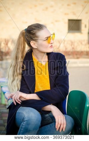 Beautiful Young Blonde Girl In A Yellow Sweater And Blue Jeans, White Sneakers And A Blue Coat Sits