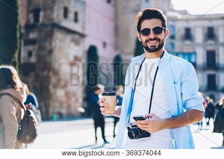 Positive Young Man In Sunglasses Strolling With Phone In Hand