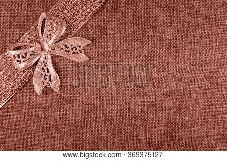 Elegant Shiny Coral Glitter Tied Bow On Coral Colored Ribbon And On Coral Natural Burlap. Horizontal