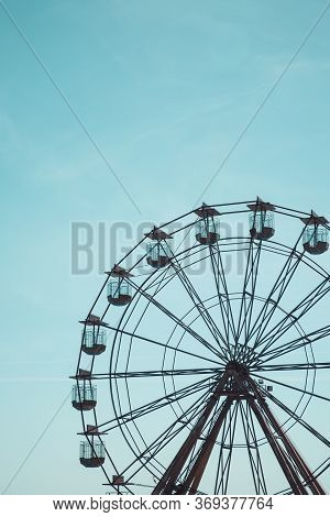 A Distant View Of A Vintage Ferris Wheel At A Seaside Fairground With Copy Space And Blue Sky Backgr
