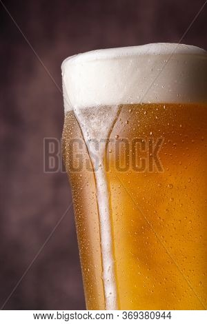 Detail Of Pint Of Cold Pale Beer With Froth Leaking Over The Glass