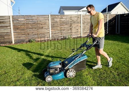 A Young Man Uses Push Lawn Mower For Mowing Grass In A Backyard. A Guy In Sunglasses In Casual Wear.