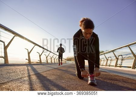 Getting Ready For Jogging. African Sporty Woman In Black Sportswear Tying Shoelaces Before Run On Th