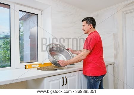 Middle Aged White Man Installs Round Single Stainless Steel Sink Into A Cut-out Hole In The Kitchen
