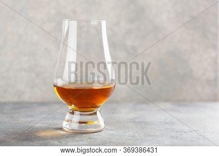 glass of whisky spirit brandy on gray concrete background