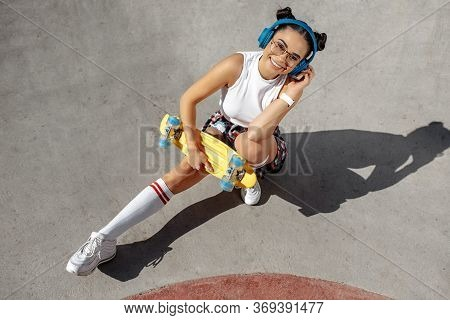 Brunette Young Woman Sitting And Listening Music Holding Yellow Skateboard Or Pennyboard At The Skat