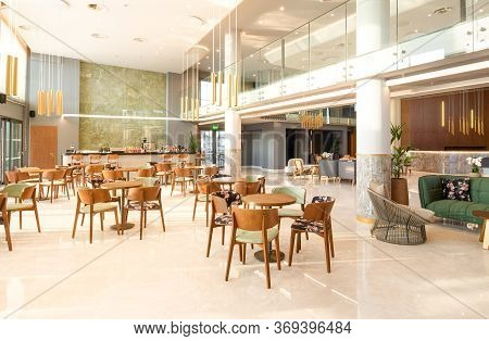 Light Wooden And Marble Tile Floor Interior Of Modern Cafe With Double Ceiling Height. Lobby Bar In