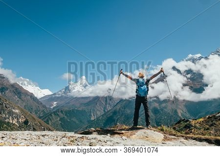 Active Vacations Concept Image. Young Hiker Backpacker Man Rising Arms With Trekking Poles Enjoying