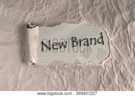 Words New Brand On Torn Brown Grunge Paper Background. Marketing Strategy, Different Trajectories In