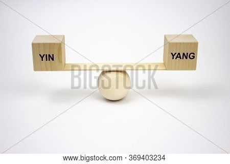Yin And Yang Balance Concept. The Inscription On Wooden Cubes That Balance On The Wooden Conceptual