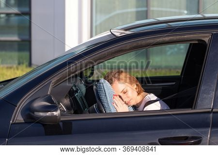 Tired Young Woman Driver Asleep On Pillow On Steering Wheel, Resting After Long Hours Driving A Car.