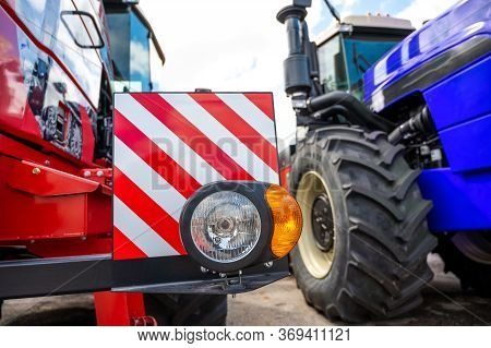 New Clean Right Headlight With A Reflector On The Bumper Of A Red Tractor