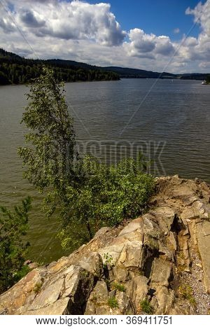 Lipno lake in Czech Republic. Birch on rock crag and cloud above water.