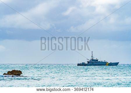 Philipsburg, Sint Maarten - November 16 2018: Caribbean island ocean view with searocks and Poema P812 (Damen Stan 4100 class Patrol Vessel) of Dutch Caribbean Coast Guard (DCCG).
