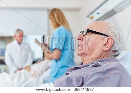 Sick senior man lying in bedside at nursing home or hospital