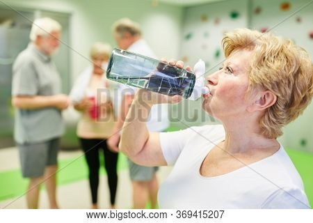 Vital senior woman quenches her thirst with water after fitness training in the climbing gym