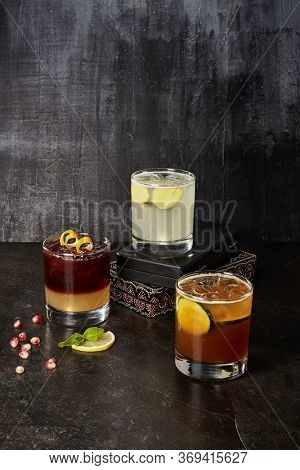 Cocktails composition on dark background. Glassfuls of alcoholic mixed drinks. Glasses with alcohol concoctions and jug of lemonade. Summer refreshing beverages with ice cubes and fruit