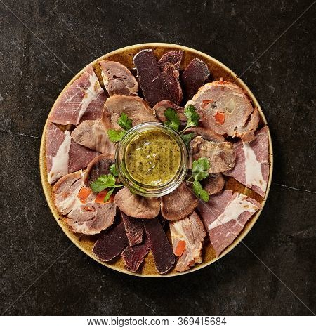 Meat plate with mustard on black marble table. Charcuterie. Cold boiled pork, sujuk, beef tongue and pastrami on plate. Meat products assortment. French cuisine. Culinary art. Traditional dish