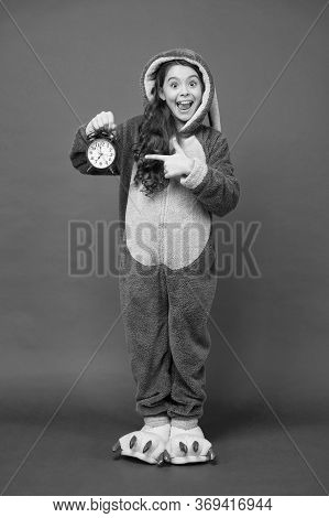 Counting Time. It Is Weekend. Adorable Bunny Hold Alarm Clock. Small Girl In Bunny Costume. Child In
