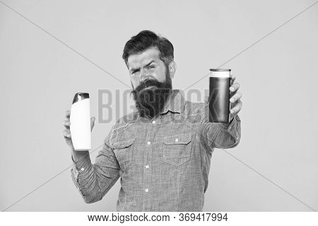 Take This Shampoo. Bearded Man Hold Shampoo Bottles Yellow Background. Hipster With Beard And Mustac