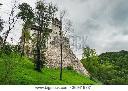 Bran Or Dracula Castle Under Blue Cloudy Sky, View From Bran Village In Transylvania, Romania