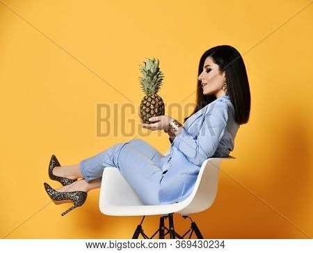 Stylish Woman In Blue Official Suit Formal Wear Sitting In Designer Armchair Sideways With A Pineapp
