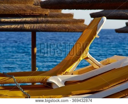 Stack Of Yellow Sun Beds And Straw Sunshades In A Tropical Beach Ready For A Great Summer Vacation