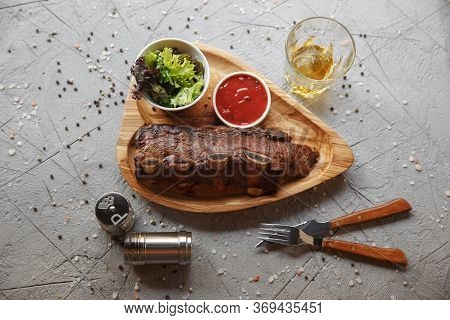 Grilled Pork Ribs Served On A Wooden Board With Salad And Sauce.