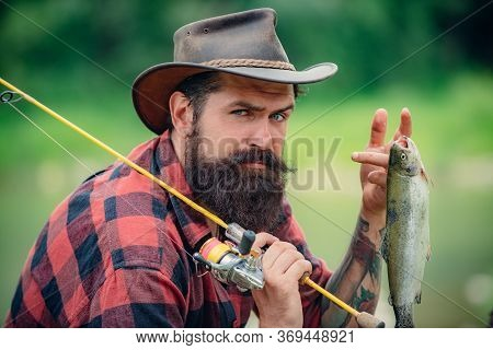 Serious Fisherman Near Water With Fish. Fisherman With Fishing Rod. Fisherman Fishing Equipment. Fis