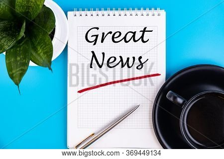The Text, The Word Great News, Is Written In A Notebook Lying On A Blue Table With A Pen. Business C